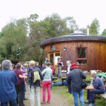 People facing a wooden cabin at the Reforesting Scotland Gathering in 2009