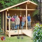 People in a self-build timber-frame hut, built just in time for the 2007 Big Tent festival